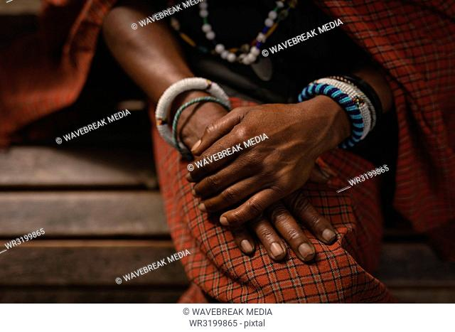 Maasai man in traditional clothing sitting on bench
