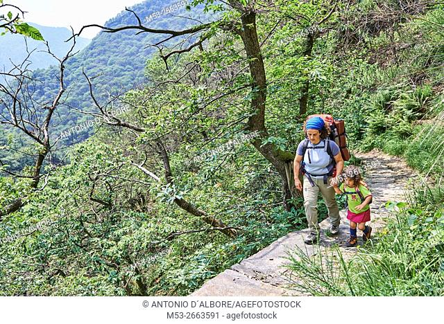 Mother and daughter hiking on a forest trail in Val Grande National Park. Verbano-Cusio-Ossola Province. Piemonte. Italy