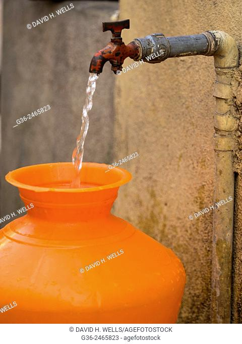 Pot filling from running water tap in Bangalore, Karnataka, India
