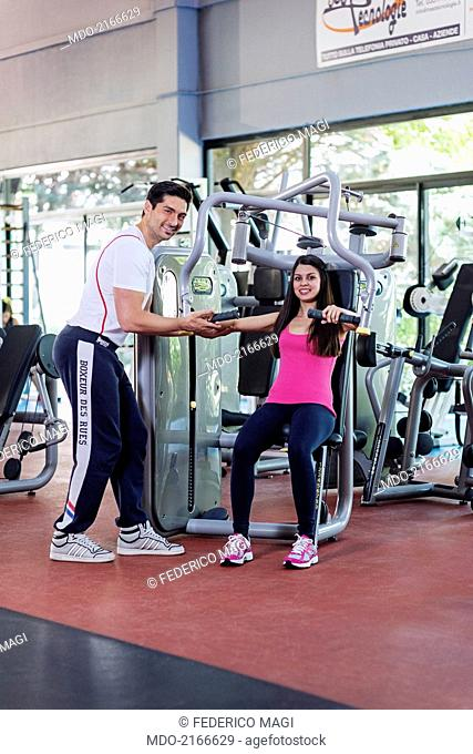 A girl at the gym, sitting at the chest press (fitness equipment) with her trainer. She worked her critical areas by a hard training