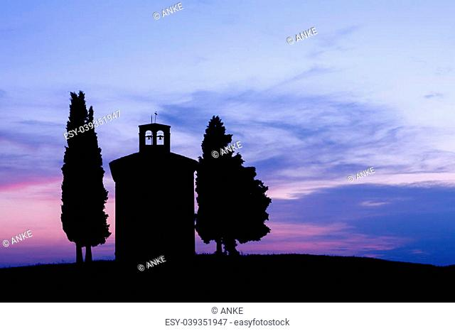 Silhouette at sunset of a chapel in Tuscany near Pienza, Italy