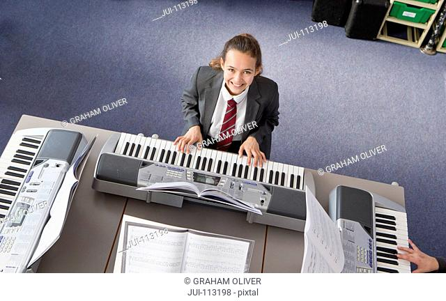 Portrait smiling high school student playing piano in music class