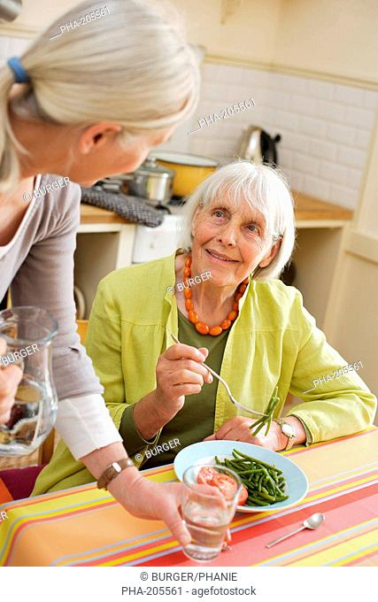 80 years old woman having lunch at home