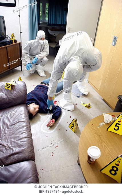 The position of a victim is marked with chalk spray, officers of the C.I.D., the Criminal Investigation Department, gathering forensic evidence at a crime scene
