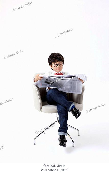 a boy sitting in a chair reading a newspaper