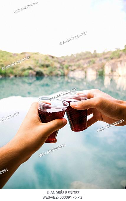 Hands of toasting men in front of a lake