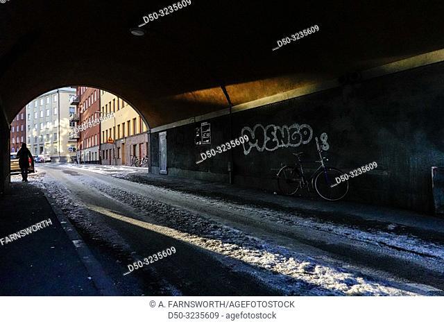 Stockholm, Sweden A pedestrian in an arched passsageway on Folkskolegatan at Hornstull on Sodermalm