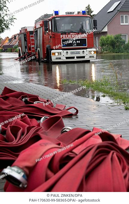 A fire engine drives along a flooded street in Leegebruch, Germany, 30 June 2017. Heavy rain on the Thursday resulted in flooding and numerous call-outs for the...