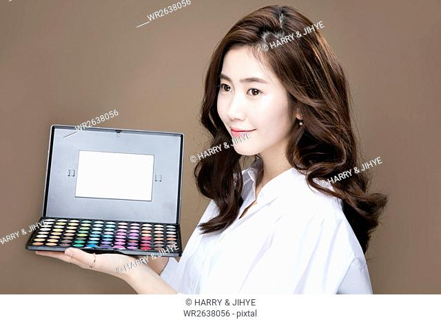 Portrait of young woman holding makeup palette