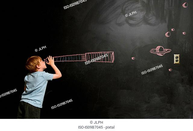 Boy looking through imaginary telescope drawn on blackboard