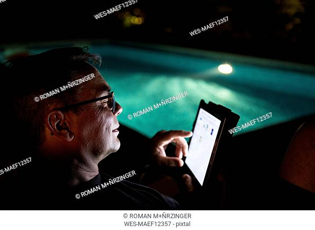 Man using tablet at the poolside at night