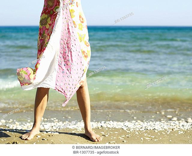 Woman wearing a beach dress fluttering in the wind on a beach on the island of Samos, Eastern Aegean Sea, Greece, Europe