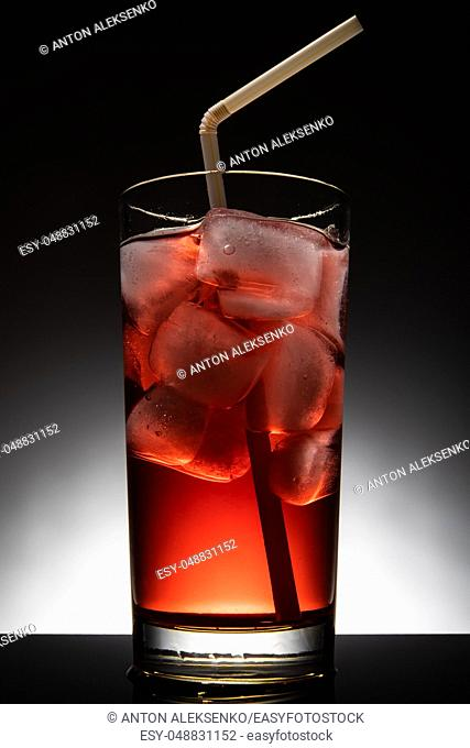 Isolated glass with a red cocktail and ice-cubes