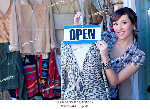 Woman hanging open sign on mannequin
