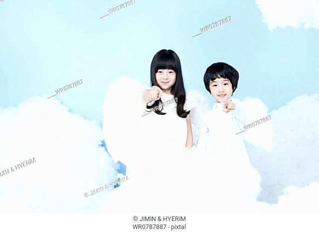 two kids with looks of angels on the clouds