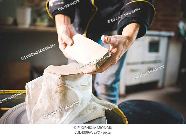 Cropped view of mid adult mans hands removing clay block from plastic bag