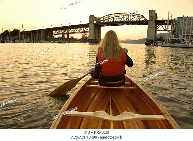 Girl canoeing in False Creek, Burrard Bridge at sunset, Vancouver, British Columbia, Canada