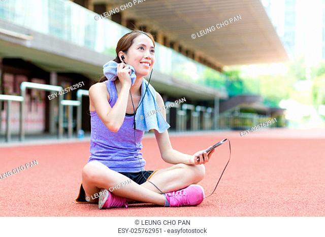 Woman take a break on sport stadium with smartphone