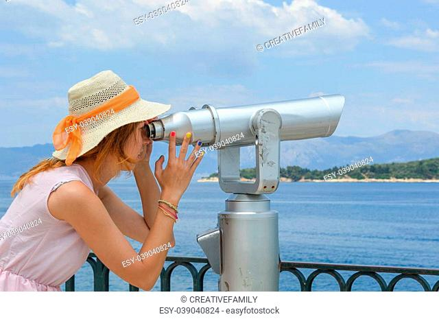 Young girl looking thru public binoculars at the seaside wearing straw hat and pink dress