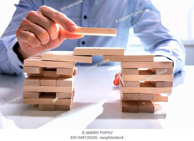 Conceptual Photo Of Businessman Building Bridge To Connect Two Towers