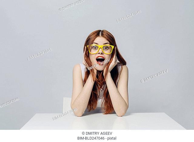 Surprised Caucasian woman sitting at table wearing yellow eyeglasses