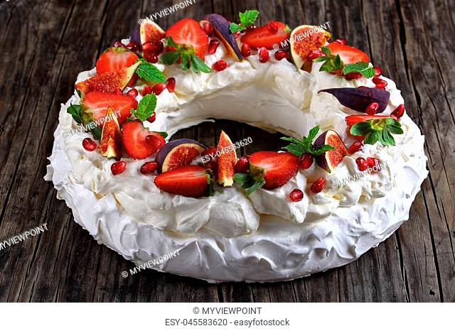 pavlova cake wreath - tender and elegant sweet dessert from french meringue and whipped cream, decorated with strawberry, figs