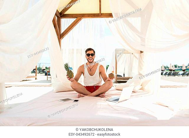 Full length portrait of cheery young man with beard sitting on luxury lounge bed with roof and curtains, pillows and mattress