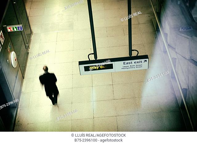 Back view of an unrecognizable executive man walking on a way out of a corridor in Canary Warf station in London, England, UK, Europe