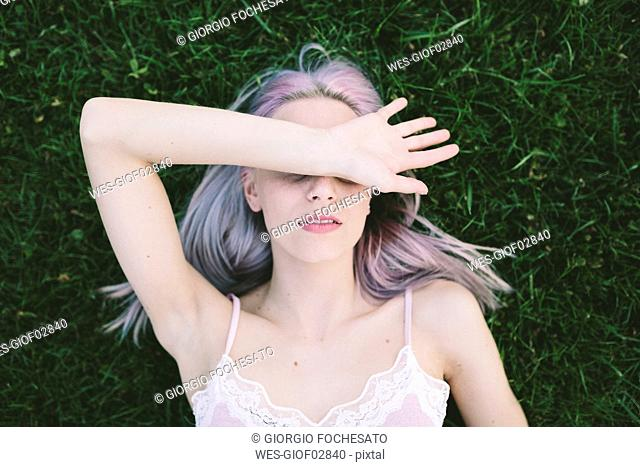Woman lying on grass covering eyes with her arm