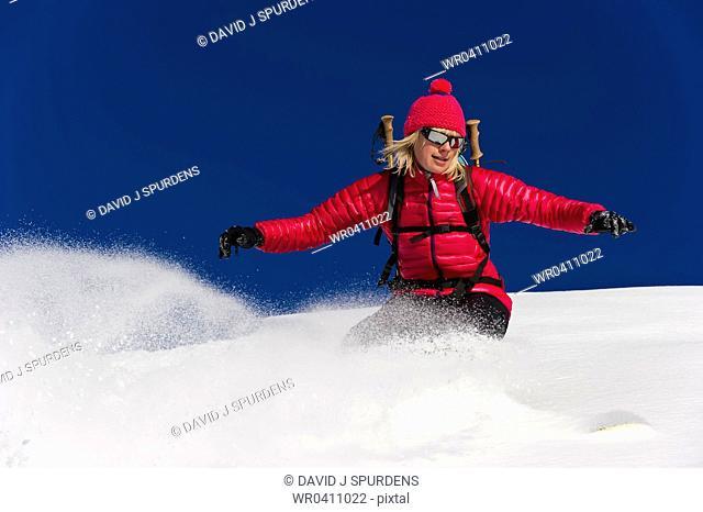 A well balanced snowboarder riding fast through the fresh powder snow