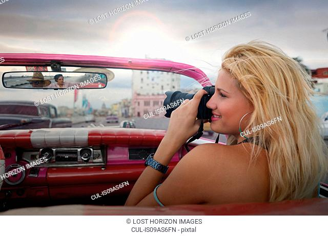Young woman taking pictures from a vintage car on the Havana' Malecon, Cuba