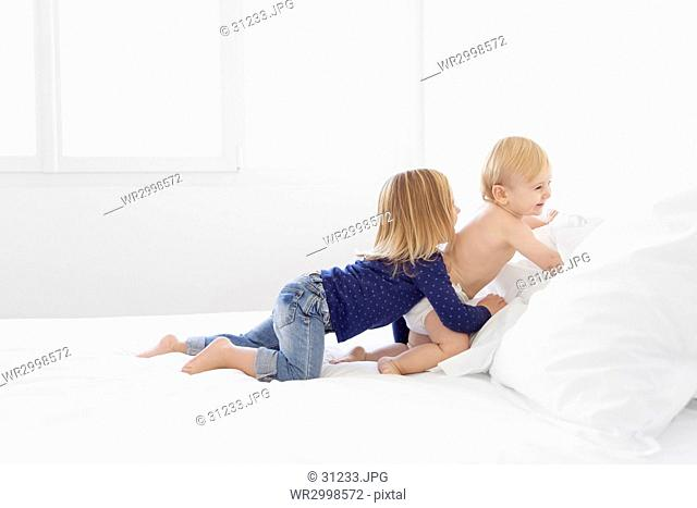 Girl with blond hair wearing jeans and blue top and baby boy kneeling on a bed, playing