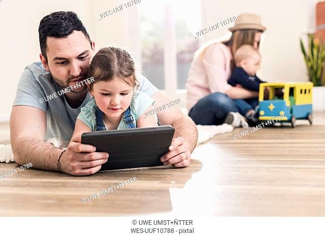 Father and daughter using tablet in new home with woman and baby in background