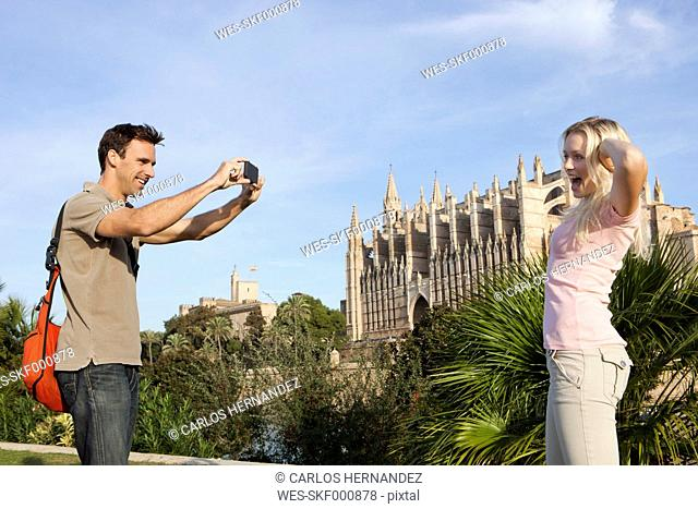Spain, Mallorca, Palma, Couple photographing with mobile phone at St Maria Cathedral