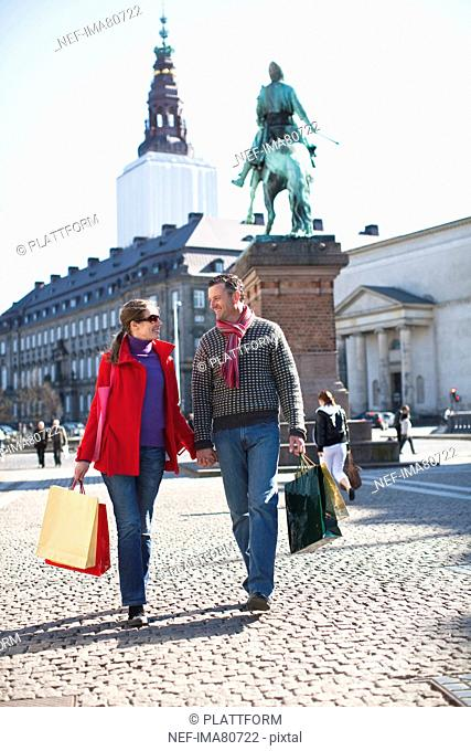 Couple with shopping bags, walking in city