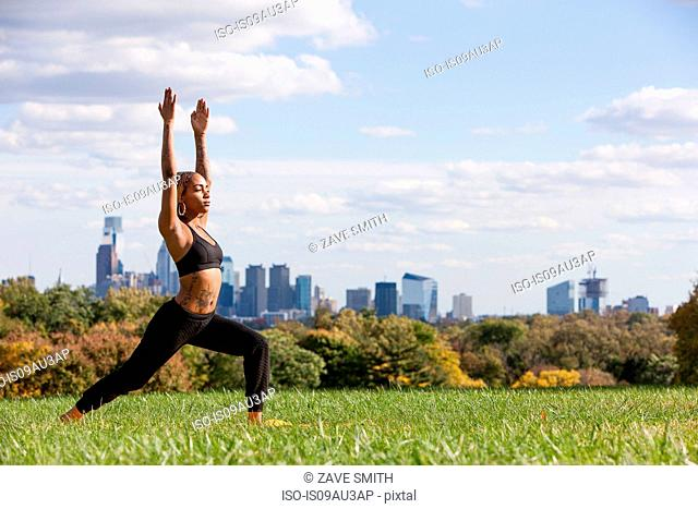 Side view of young woman on grass in yoga position, arms raised, eyes closed, Philadelphia, Pennsylvania, USA