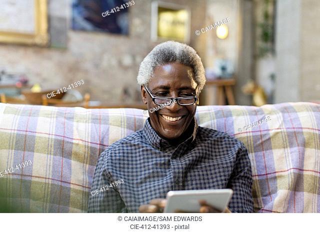 Smiling senior man using digital tablet on sofa