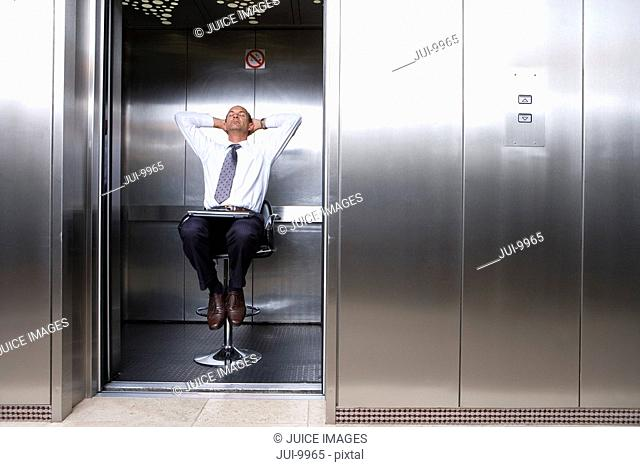 Mature businessman on stool in lift, laptop on lap, leaning back with head in hands