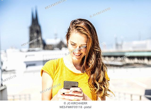 Germany, Cologne, smiling woman using cell phone