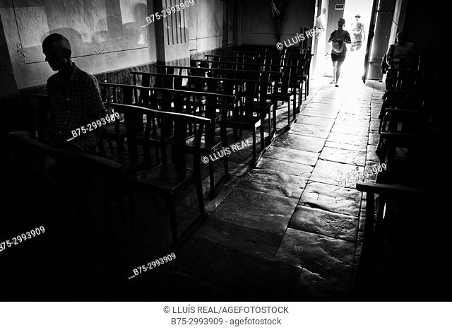 Silhouettes of unrecognizable people entering church. Corte, Corsica, France