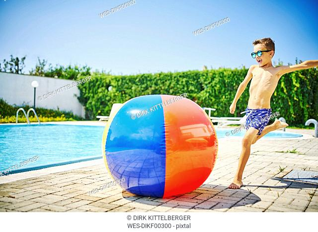Boy at the poolside sunglasses kicking great beach ball