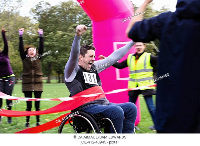 Enthusiastic man in wheelchair crossing charity race finish line