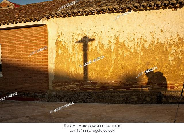 Shadow of a pilgrim and cross on a wall along the Camino de Santiago