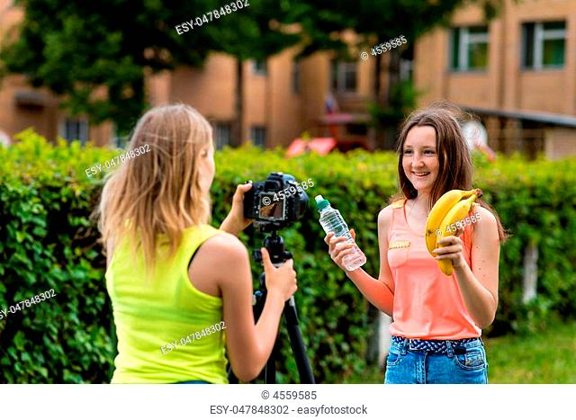 Two young girls. Summer in nature. Tells about proper nutrition. In hands of bottle of water and bananas. Record vlog and blog subscribers