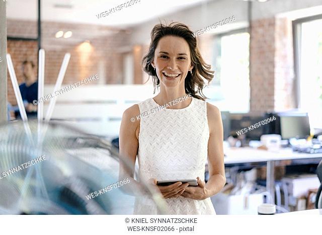 Businesswoman in office enjoying breeze from a fan