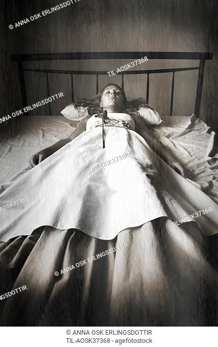 Lone female figure wearing dress lying in bed