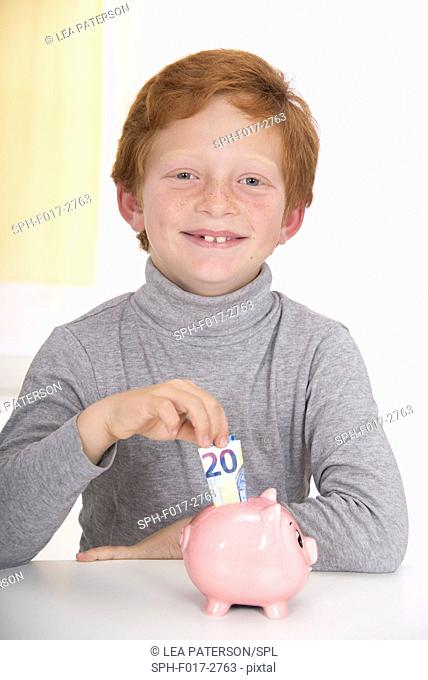 MODEL RELEASED. Boy putting money in piggy bank, smiling