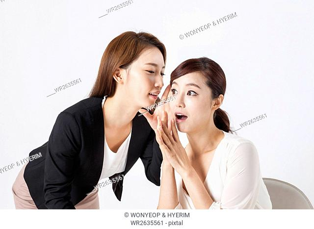 Two young smiling businesswomen talking in a whisper