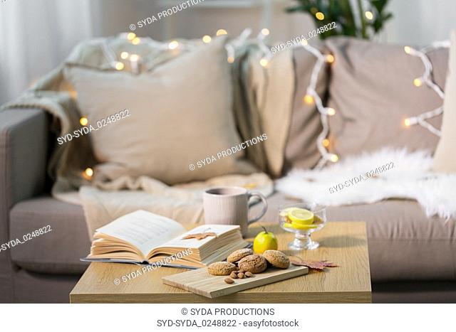 oat cookies, book, tea and lemon on table at home