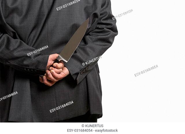 Man in suit hiding a large knife behind his back isolated on white background